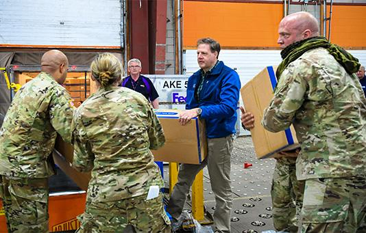 Governor Sununu helping load supplies with the National Guard